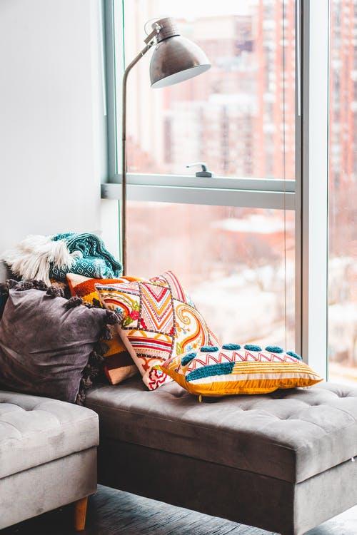 farverige puder på på sofa foran vindue